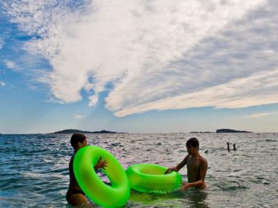 Stranden består av klappersten, men i det klara vattnet är det en len fin sandbotten.
